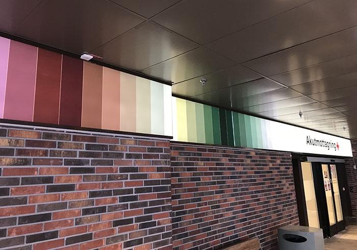 En rad upplysta färgfält löper längs husets vägg nära taket fram till akutingångens entré