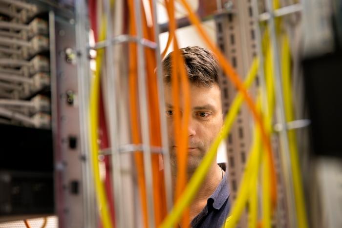 En medarbetare på Regionarkivet står delvis skymd bakom ett stort antal datakablar