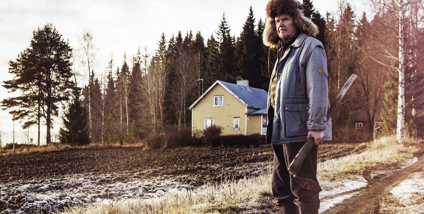 Äldre man med pälsmössa och gevär framför ett hus i öppen naturmiljö.
