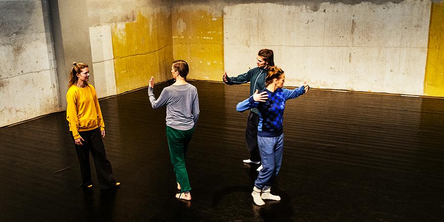 Fyra dansare i en tom lokal med betongväggar med gulmålade inslag.