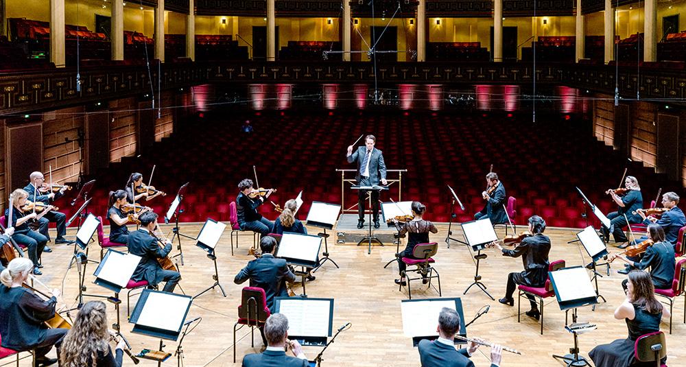 Foto som visar orkestern med en dirigent framför sig.