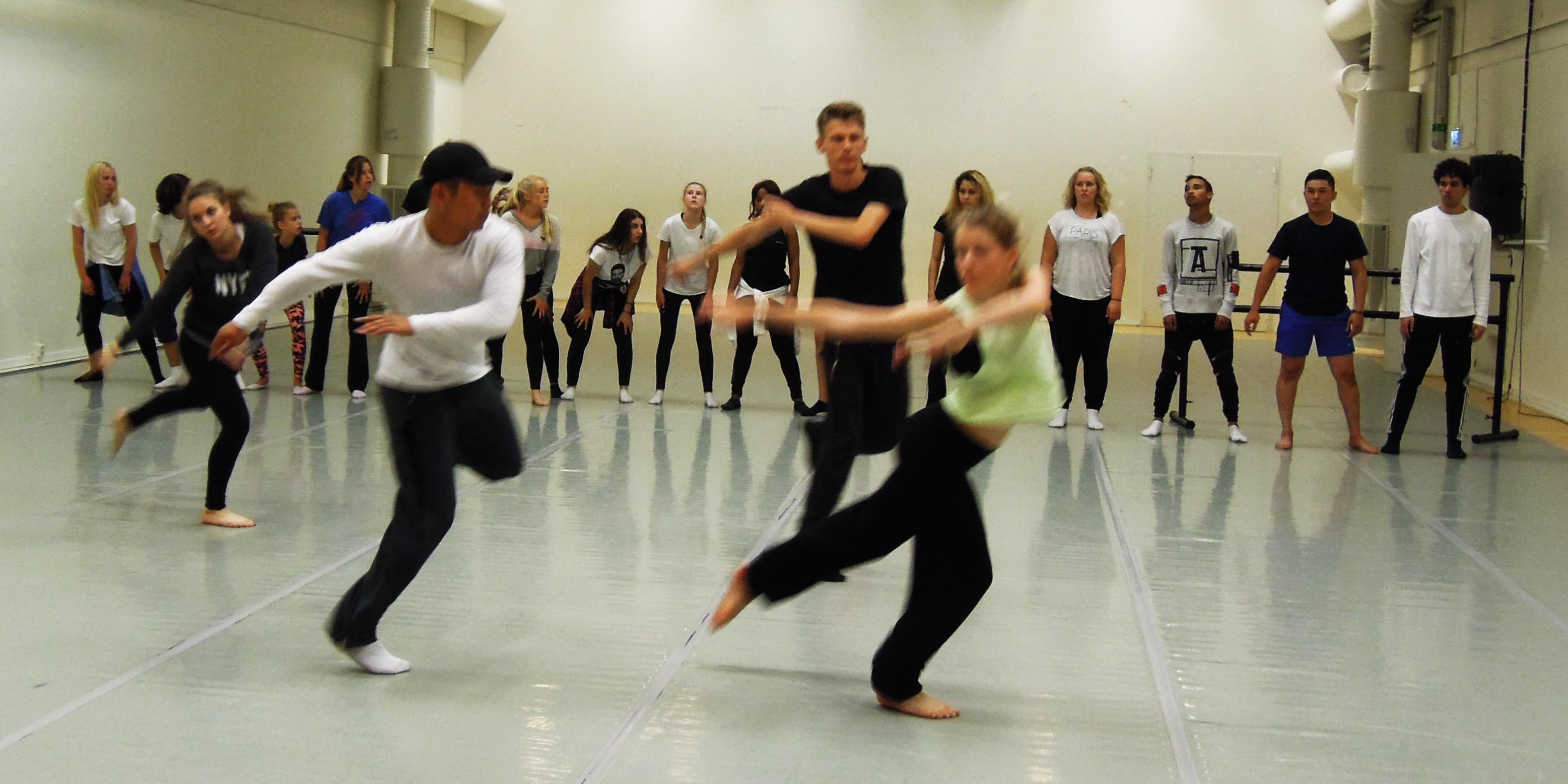 Tjejer och killar som dansar i en studio.