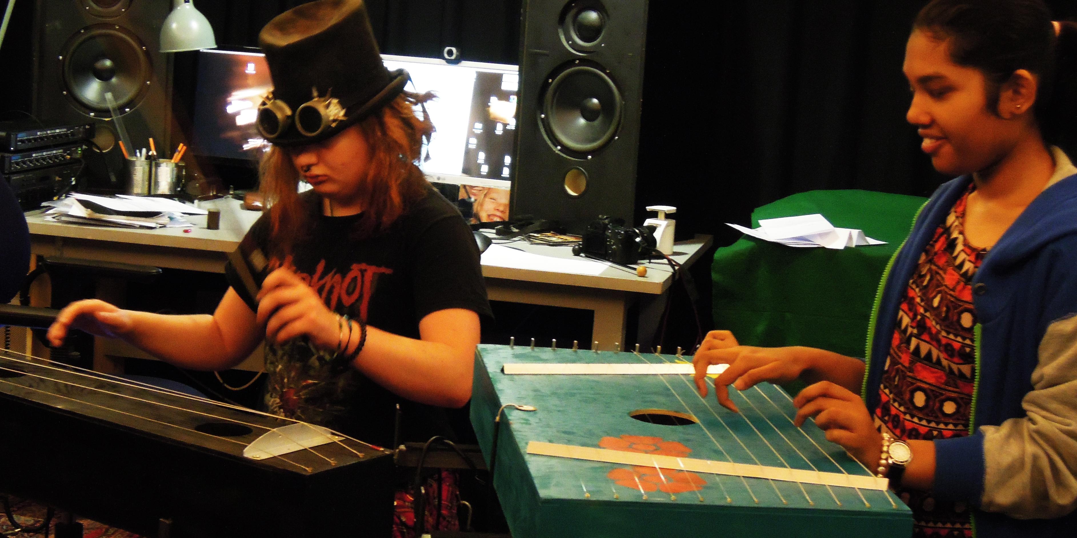 En pojke och en flicka spelar på strängnstrument med stråke respektive händer.