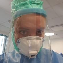 Ett ansikte med skyddsmask och visir tittar in i kameran