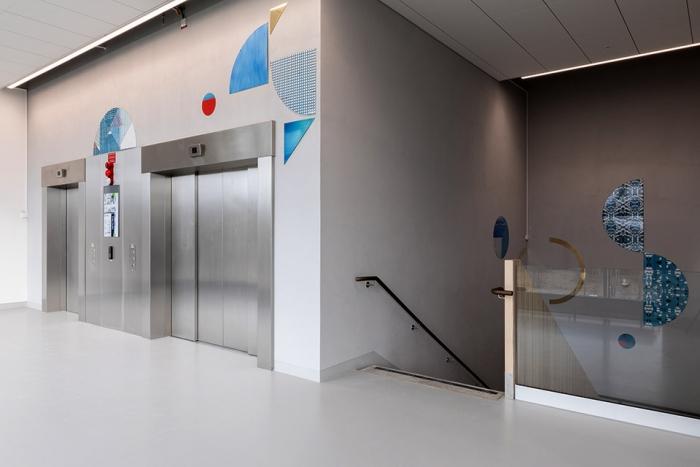 Foto av färgglada emaljer på hisshallens grå väggar av konstnären Alexandra Severinsson