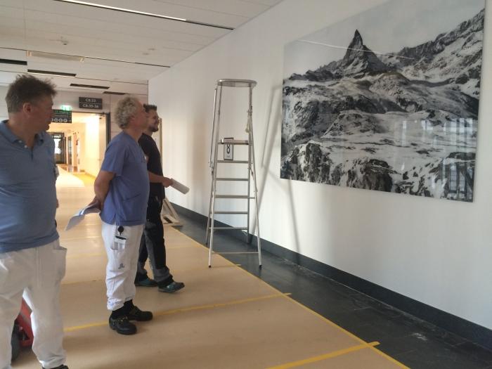 Konst installeras på sjukhus. Personal betraktar verket.